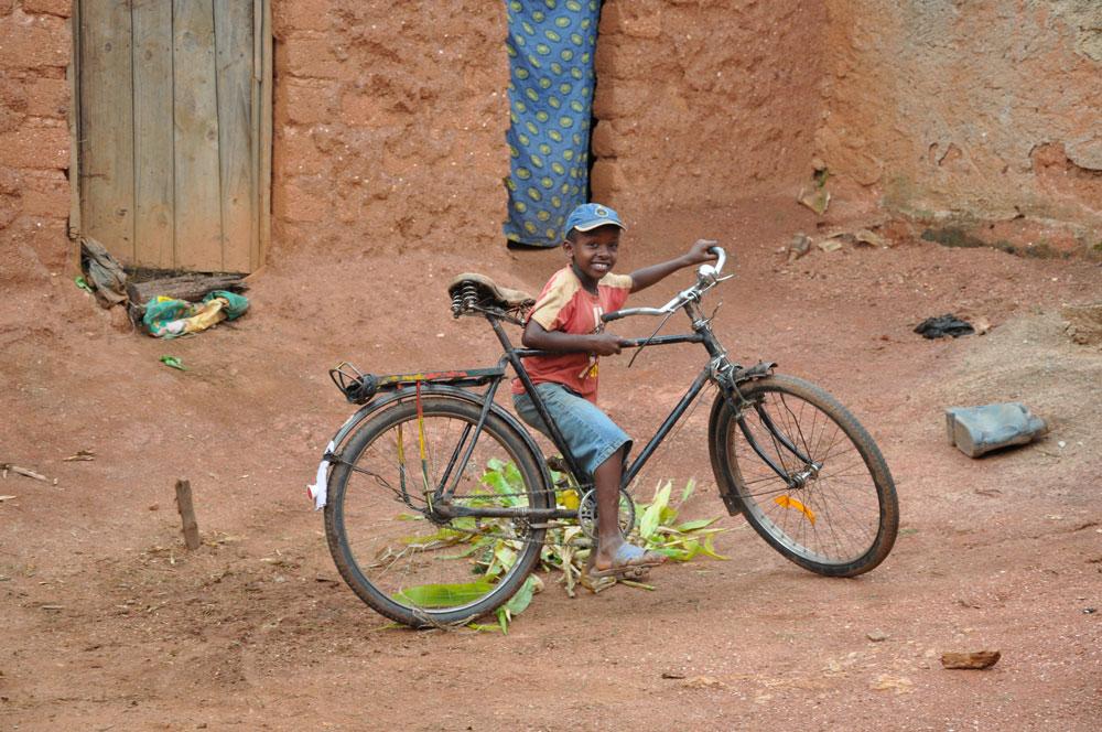 Dag Emanuells äldsta son cyklar på bakgården till deras hus